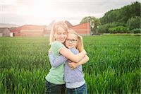 preteen girl pigtails - Portrait of nine year old girl and sister hugging in field Stock Photo - Premium Royalty-Freenull, Code: 649-07710662