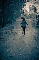 running away scared - Young woman running from danger up dirt track toward apartment blocks Stock Photo - Premium Royalty-Freenull, Code: 649-07710712