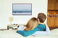 plasma - Couple watching television in living room Stock Photo - Pr