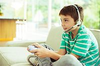 Boy playing video games on sofa Stock Photo - Premium Royalty-Freenull, Code: 6113-07730511