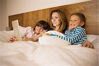 Mother and children using digital tablet in bed Stock Photo - Premium Royalty-Freenull, Code: 6113-07730567