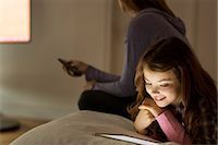 Girl using digital tablet on bed Stock Photo - Premium Royalty-Freenull, Code: 6113-07730584