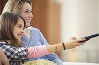 Mother and daughter watching television in living room Stock Photo - Premium Royalty-Freenull, Code: 6113-07730589