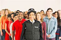 female police officer happy - Portrait of smiling policewoman in front of large crowd Stock Photo - Premium Royalty-Freenull, Code: 6113-07730656