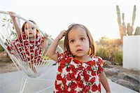 Twin baby girls playing on patio Stock Photo - Premium Royalty-Freenull, Code: 6113-07730807