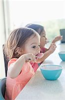 Sisters eating breakfast together Stock Photo - Premium Royalty-Freenull, Code: 6113-07730811