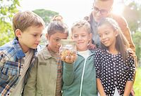 Student and teacher examining insects in jar outdoors Stock Photo - Premium Royalty-Freenull, Code: 6113-07731139