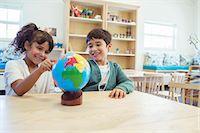 Students examining globe in classroom Stock Photo - Premium Royalty-Freenull, Code: 6113-07731269