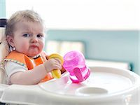 sad child sitting - Baby girl playing with sippy cup in high chair Stock Photo - Premium Royalty-Freenull, Code: 6113-07731329