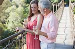 Couple toasting each other on wooden rope bridge