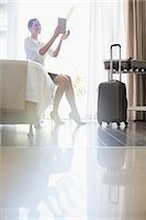 Businesswoman using digital tablet in hotel room Stock Photo - Premium Royalty-Freenull, Code: 6113-07731638