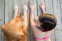 preteen bikini - A young girl and a golden retriever dog side by side on a jetty. Stock Photo - Premium Royalty-Freenull, Code: 6118-07731786