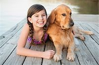 preteen girl - A young girl and a golden retriever dog lying on a jetty. Stock Photo - Premium Royalty-Freenull, Code: 6118-07731787