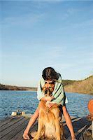 A girl cuddling a golden retriever dog. Stock Photo - Premium Royalty-Freenull, Code: 6118-07731804