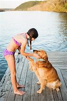 A girl in a bikini with a golden retriever dog lifting its paw up. Stock Photo - Premium Royalty-Freenull, Code: 6118-07731808
