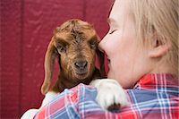 preteen kissing - A girl cuddling a baby goat. Stock Photo - Premium Royalty-Freenull, Code: 6118-07731891