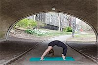 stretching (people exercising) - A young woman in Central Park, in a black leotard and leggings, doing yoga. Stock Photo - Premium Royalty-Fre