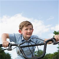 A young boy leaning over the handlebars of a bicycle. Stock Photo - Premium Royalty-Freenull, Code: 6118-07732006