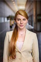 Portrait of confident young businesswoman in office corridor Stock Photo - Premium Royalty-Freenull, Code: 614-07735228