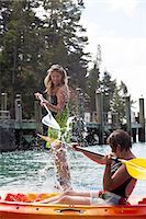 Senior woman and daughter splashing each other from kayak and paddleboard Stock Photo - Premium Royalty-Freenull, Code: 614-07735239