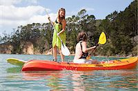 Senior woman and daughter playfighting from kayak and paddleboard Stock Photo - Premium Royalty-Freenull, Code: 614-07735240