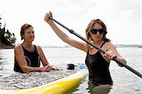 Senior woman and daughter wading with paddleboard at sea Stock Photo - Premium Royalty-Freenull, Code: 614-07735242