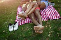 Cropped image of young couple in lying in park on picnic blanket Stock Photo - Premium Royalty-Freenull, Code: 614-07735393