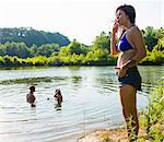 Young woman smoking cigarette on canal bank, Delaware Canal State Park, New Hope, Pennsylvania, USA