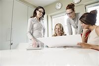 Four female designers looking at blueprint in office Stock Photo - Premium Royalty-Freenull, Code: 649-07736462