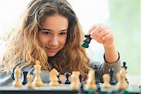 Portrait of young girl playing chess Stock Photo - Premium Royalty-Freenull, Code: 649-07736670