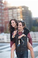 Mid adult man giving girlfriend piggyback in street Stock Photo - Premium Royalty-Freenull, Code: 649-07737040