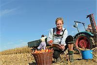 family apple orchard - Mature man checking digital tablet in front of basket with apples, woman and son in background, Bavaria, Germany Stock Photo - Premium Royalty-Freenull, Code: 6121-07739948