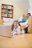 pantyhose kid - Granddaughter using laptop in living room while grandparents in background Stock Photo - Premium Royalty-Freenull, Code: 6121-07740285