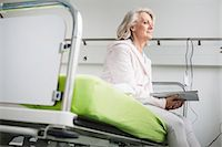 Patient in hospital sitting on bed Stock Photo - Premium Royalty-Freenull, Code: 6121-07740458