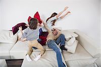 Family doing pillow fight on couch Stock Photo - Premium Royalty-Freenull, Code: 6121-07740949