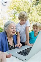 Grandmother and her two grandsons looking at laptop Stock Photo - Premium Royalty-Freenull, Code: 6121-07741211