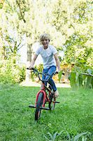 Young boy cycling in the garden Stock Photo - Premium Royalty-Freenull, Code: 6121-07741223