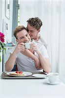Homosexual couple having breakfast together, smiling Stock Photo - Premium Royalty-Freenull, Code: 6121-07741295