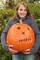 preteen  smile  one  alone - Girl holding halloween lantern, smiling, portrait Stock Photo - Premium Royalty-Freenull, Code: 6121-07741422