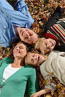 Family lying on autumn leaves, smiling Stock Photo - Premium Royalty-Freenull, Code: 6121-07741434