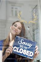 person holding sign - Portrait of sales girl holding closing board of fashion shop, smiling Stock Photo - Premium Royalty-Freenull, Code: 6121-07741506
