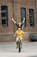 Portrait of teenage couple riding bicycle, smiling Stock Photo - Premium Royalty-Freenull, Code: 6121-07741545