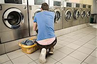 Young man filling up cloths in machine Stock Photo - Premium Royalty-Freenull, Code: 6121-07741561