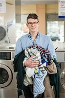 Portrait of young man with laundry, smiling Stock Photo - Premium Royalty-Freenull, Code: 6121-07741584
