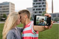 Teenage couple taking self portrait with themselves Stock Photo - Premium Royalty-Freenull, Code: 6121-07741631