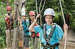 Boys and girls climbing crag, smiling