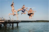 preteen girls bath - Five teenagers jumping from a jetty into lake Stock Photo - Premium Royalty-Freenull, Code: 6121-07741791