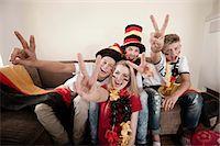 Teenage soccer fans posing in living room Stock Photo - Premium Royalty-Freenull, Code: 6121-07741922