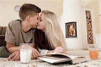 Teenage couple in love cuddling on carpet in front of fireside Stock Photo - Premium Royalty-Freenull, Code: 6121-07741932
