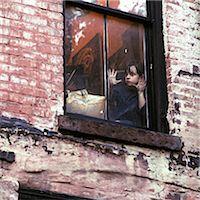 sad child sitting - 1960s 1970s SINGLE SAD LITTLE GIRL SITTING IN WINDOW OF WORN URBAN BRICK BUILDING Stock Photo - Premium Rights-Managednull, Code: 846-07760707